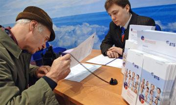 Мужчина и сотрудник банка читают документы